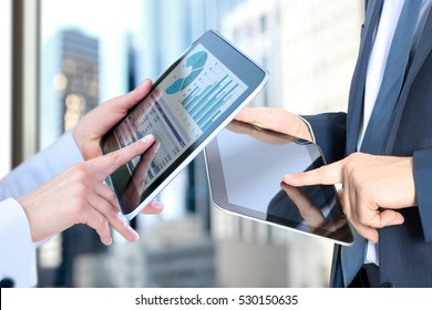 Business woman  and man working and analyzing financial figures on a graphs