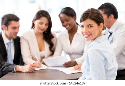 Business woman in a meeting at the office smiling