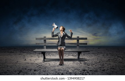 Business woman with megaphone sitting on wooden bench. Female speaker shouting in loudspeaker outdoors. Business marketing and promotion. Beautiful skyscape with deep blue night sky.