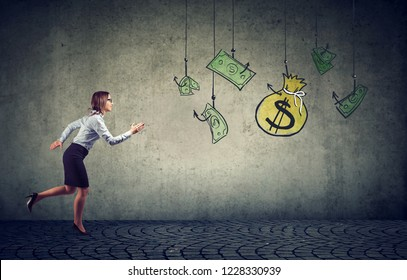 Business woman motivated by money hanging on a fishing hook. Businesswoman running for cash dollar