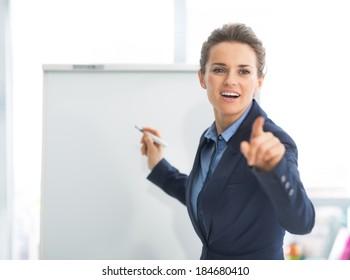 Business woman near flipchart pointing on listener