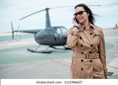 Business woman near private helicopter