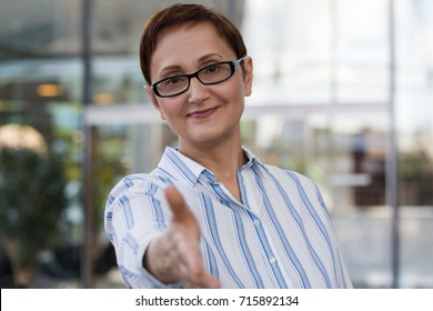 Business woman offers her hand for handshake. Professional portrait of 40 50 years old businesswoman in the office. Deal / contract / successful negotiation / business agreement concept.