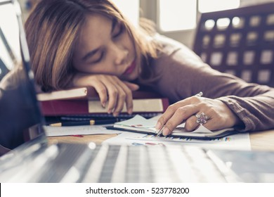 business woman in the office Tired overworked woman resting while she was working writing notes, overwork and stress concept.