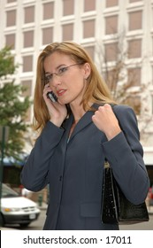 Business woman on cell phone holding purse in front of office building