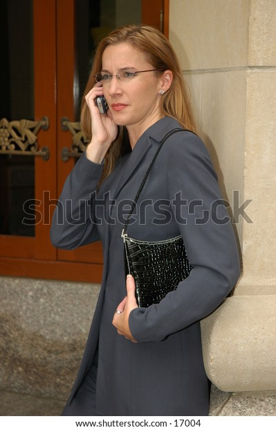 Business woman on cell phone wearing glasses holding purse