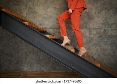 A business woman in an orange business suit climbs up the stairs. Career ladder. High-heeled shoes. Gray background