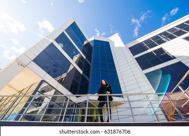 Business woman outdoors talking at the phone with modern building as background.