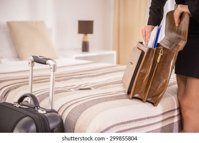 Business woman packing his things into the briefcase on the bed at the hotel room. Close-up.
