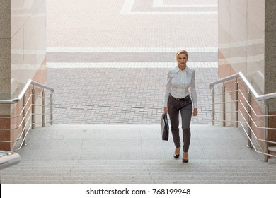 Business woman in pants with a briefcase climbs the stairs