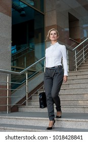 Business woman in pants with briefcase walking on stairs