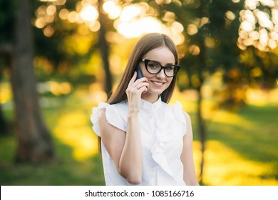 Business woman in the park using phone
