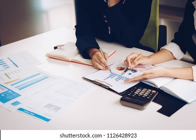 Business woman and partner hand pointing at finance chart for planning about marketing, tax, accounting, statistics and analytic research concept.