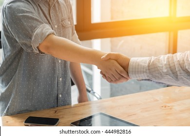 Business woman and partner shaking hands in office