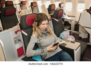 Business woman passenger listening to music and relaxing during the flight by airplane in first class. Comfortable, luxury travel