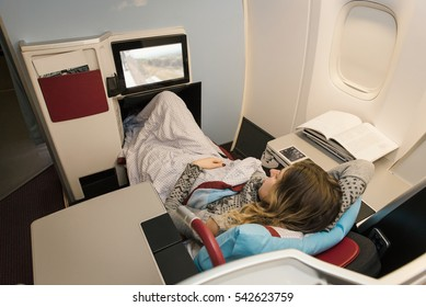 Business woman passenger watching movies and relaxing during the flight by airplane in first class. Comfortable, luxury travel