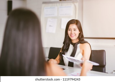 Business woman passing document to manager at the office .The office worker submits a report on the work done to the head.