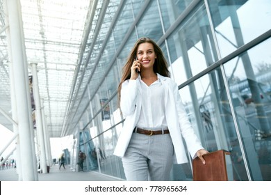 Business Woman With Phone Near Office. Portrait Of Beautiful Smiling Female In Fashion Office Clothes Talking On Phone While Standing Outdoors. Phone Communication. High Quality Image.