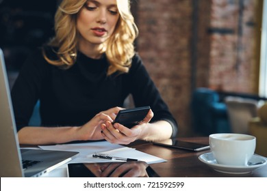 business woman with phone working on desk documents and laptop