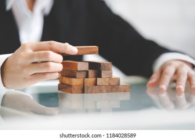 Business woman placing wooden block on a tower concept risk control, planning and strategy in business.