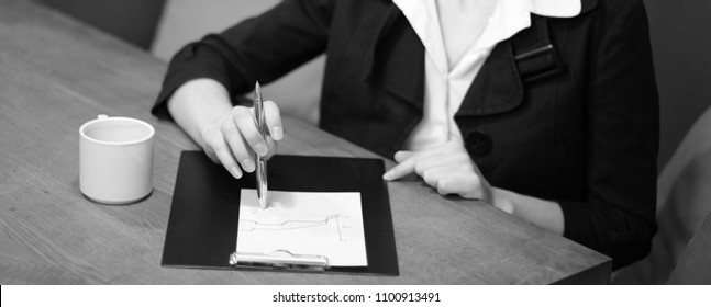 Business woman. Planning. Online sales. Success. Office work. Time is money. Sales. Graph, increase. A pen in hand. Write. Make notes. Hands on table.
