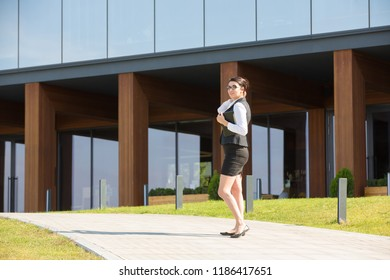 Business woman plus size stands on the background of an office building with a tablet in hand.