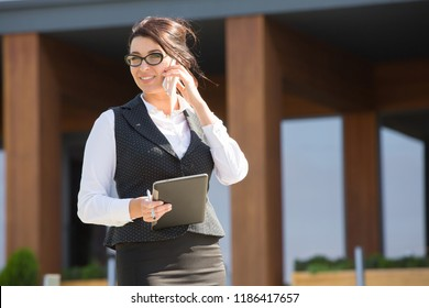 Business woman plus size stands on the background of an office building with a tablet in hand. The lady is talking on her mobile phone