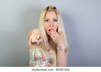 Business woman point finger at you looking at camera on gray background