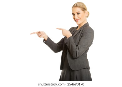 Business woman pointing at copyspace on the left.