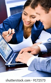 Business woman pointing at laptop and explaining a plan of work to colleague
