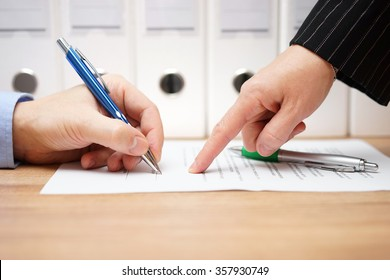 business woman is pointing where to sign on document, with documents in background