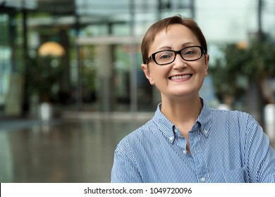 Business woman. Portrait of middle aged 40 50 years old female wearing shirt and glasses in the office.