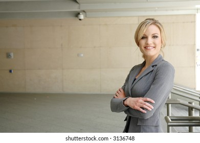 business woman is posing in front of some business buildings smiling happily