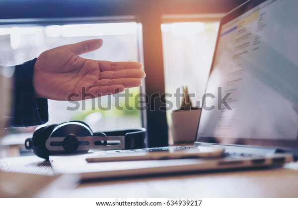 A business woman presenting her work in laptop with smart phone and headphone in office
