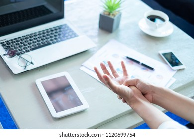 Business woman pressing the middle of her palm with her thumb to relieve pain due to a tendinitis caused by an excessive use of computer, laptop, phone.