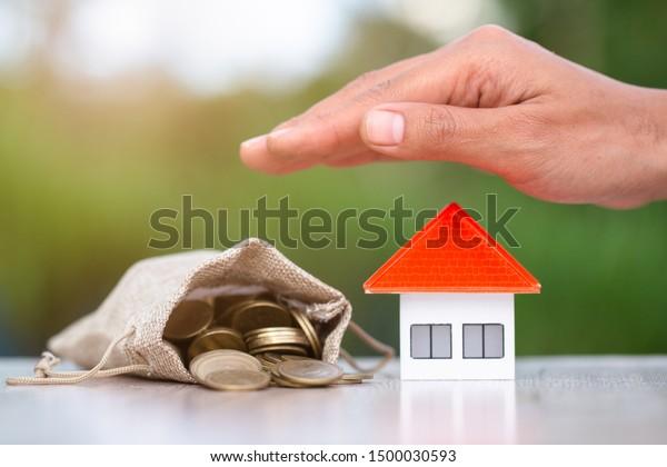 ビジネスマンは、大量のコインの山の近くに置かれた家を守る。プロパティ管理のアイデア。投資とリスク管理資産の管理夢の家のお金を節約する不正を防ぐ。