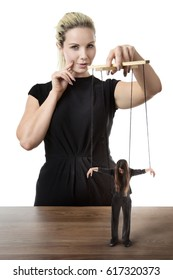 business woman puppet master pulling on strings of a doll