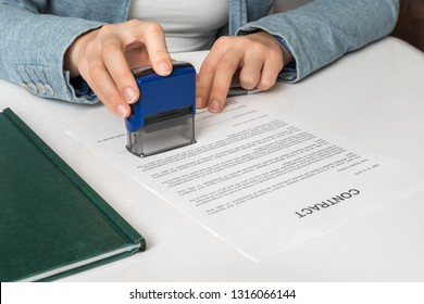 Business woman putting stamp on documents in the office - signing contract concept
