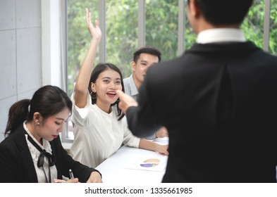 Business woman raise her hands to present her opinions at the meeting for business concept