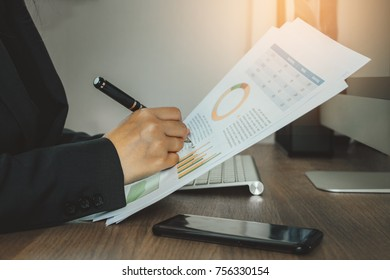 Business woman reading and checking documentation on her working space