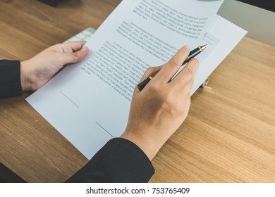 Business woman reading terms and condition paper on table, signing concept