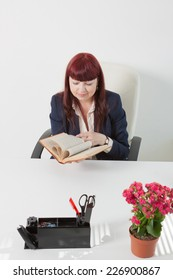 business woman reads book in a comfortable modern office