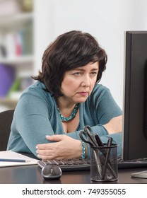 Business woman reads fake news on a office computer with distrustful. She crosses her arms sitting at the black desk and looks at monitor attentively. Indoors background is blurred. Vertical shot