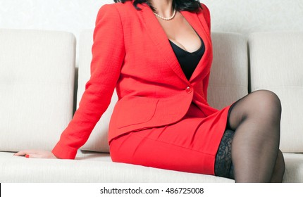 business woman in red formal suit sitting on a white couch