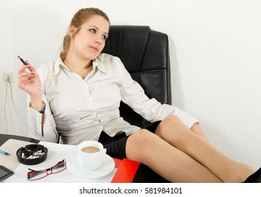 Business woman resting, drinking coffee and smoking cigarette at the end of working day.