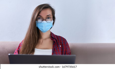Business woman in round glasses wears medical protective mask working from home at the computer during self-isolation and quarantine. Coronavirus outbreak and covid epidemic. Stay home. Copy space