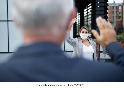 Business woman with safety mask and man greeting by waving hands in front of office building. Virus protection and social distancing concept at work