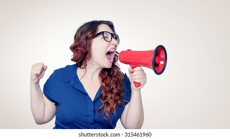 Business woman screaming into a megaphone
