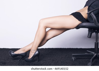 Business woman seated on a chair showing her sexy legs, with lingerie, and heel shoes over a white background.