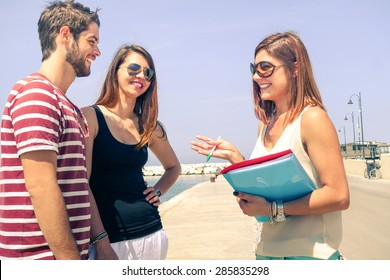 Business woman selling property to young cheerful couple for summer vacations -  Happy tourists on trip location talking with female broker - People concept of real estate sale in travel destination
